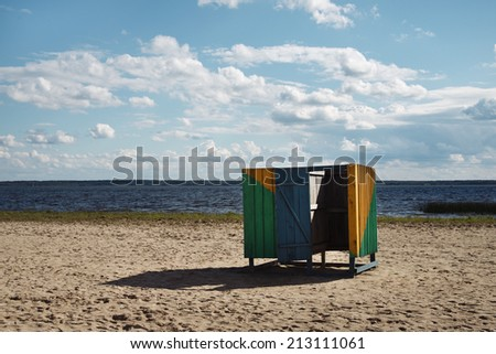 wooden cubicle changing rooms on beach - stock photo
