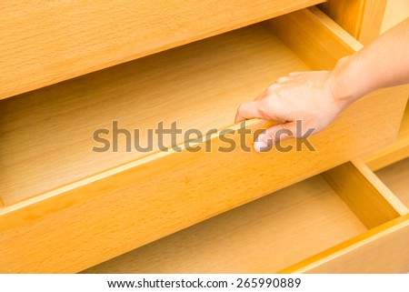 wooden cupboard with hand opened empty drawers - stock photo