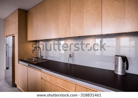 Wooden cupboards and black worktop in modern kitchen - stock photo