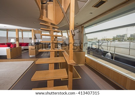 Wooden curved staircase in salon area of large luxury motor yacht - stock photo