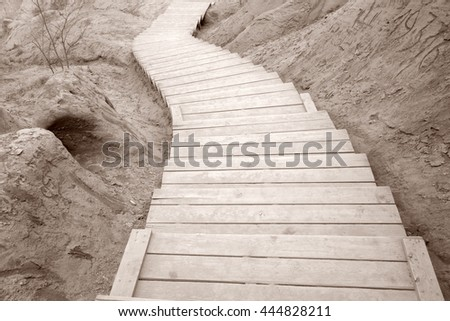 Wooden Curved Stairway on Clay Background in Black and White Sepia Tone