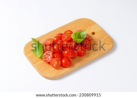 wooden cutting board with halved cherry tomatoes decorated with fresh basil - stock photo