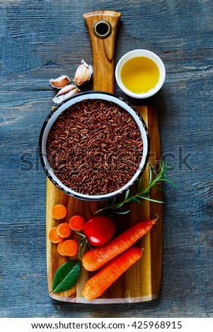Wooden cutting board with raw red rice and fresh vegetables ingredients for tasty cooking over dark rustic background, top view.  Healthy eating or vegetarian concept. - stock photo