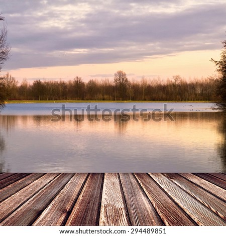 Wooden deck floor on sunset lake with trees and sky - stock photo