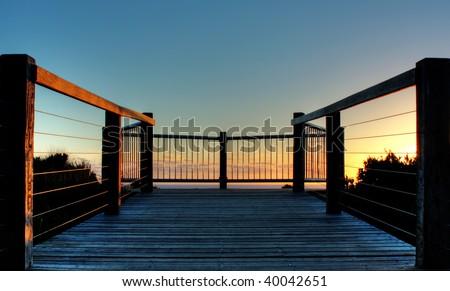 Wooden deck on coastline of Great Ocean Road, Australia during sunset - stock photo