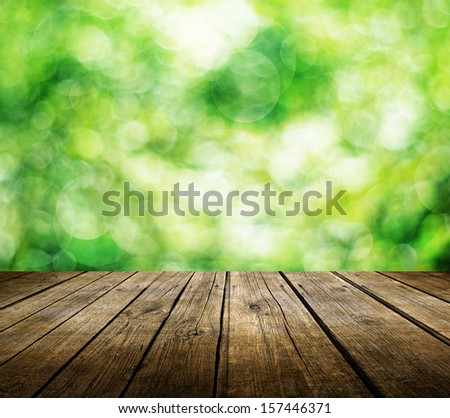 Wooden deck table over beautiful green background - stock photo