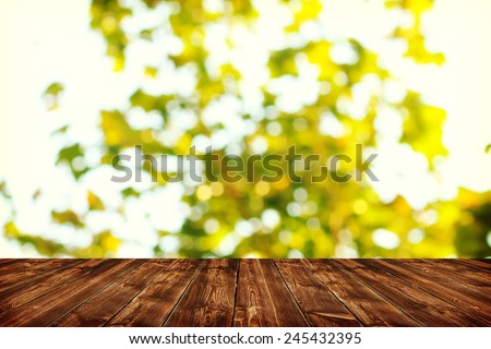 Wooden deck table with spring bokeh background - stock photo