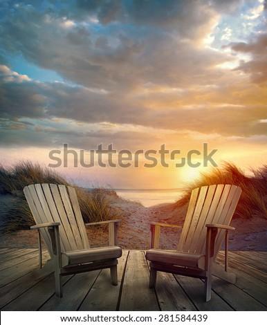 Wooden deck with chairs, sand dunes and ocean at sunset - stock photo