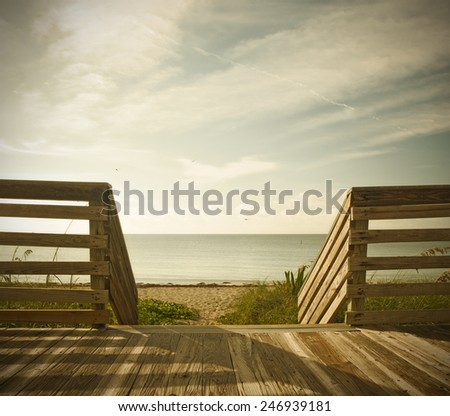 Wooden deck with fence overlooking the ocean and the beach in the famous tourist destination of Key West in Florida Keys. Desaturated filter processing for instagram looks - stock photo