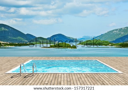 Wooden deck with swimming pool with beautiful view of sea and mountains - stock photo