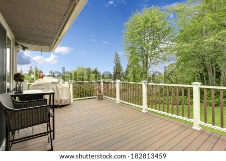 Wooden deck with white and brown railings. Patio table with wicker chairs and barbecue - stock photo