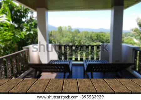 wooden deckchair at the balcony and terrace with forest and sky view (blur background with wood table top for display or montage your product) - stock photo