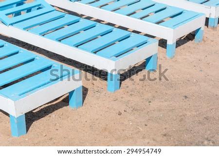 wooden deckchairs on the sand beach - stock photo