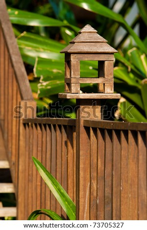 Wooden designed handrail of a pathway outsied of a garden. - stock photo