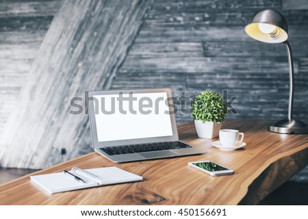 Wooden designer desktop with blank white laptop, stationery items, coffee cup, cell phone, plant and table lamp. Mock up - stock photo