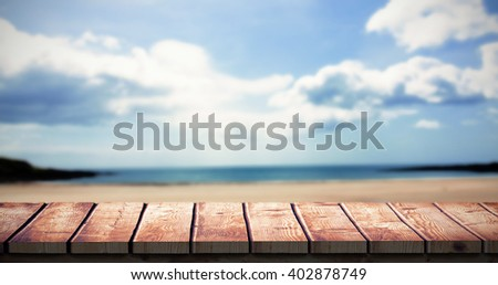 Wooden desk against beach with blue sky - stock photo