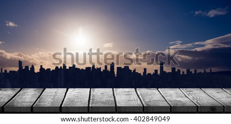 Wooden desk against picture of a city by sunrise