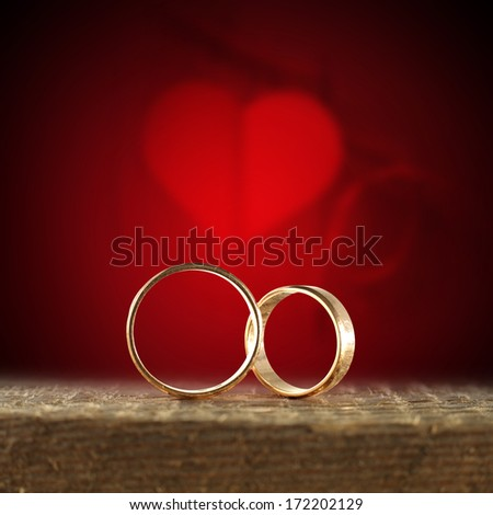 wooden desk and gold weeding rings  - stock photo