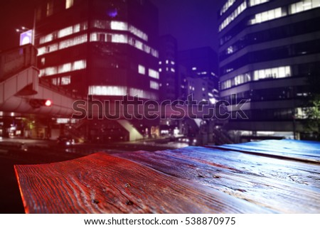 wooden desk in city with night background and party time