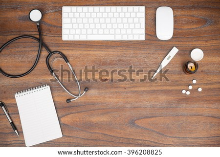 Wooden desk with a computer, notepad, stethoscope and some pills in a physician's office - stock photo