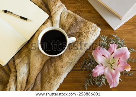 Wooden desk with a cup of coffee, notebook and flower. Soft fur on the table creates a girly, romantic and cozy atmosphere.