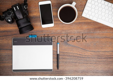 Wooden desk with a pen tablet, a dslr and a smartphone seen from above - stock photo