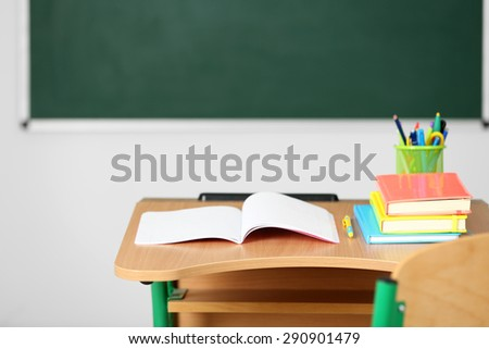 Wooden desk with stationery and chair in class on blackboard background - stock photo
