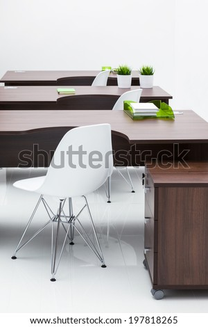 wooden desks and white plastic chairs in the office