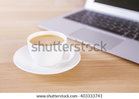 Wooden desktop with coffee cup and laptop keyboard - stock photo