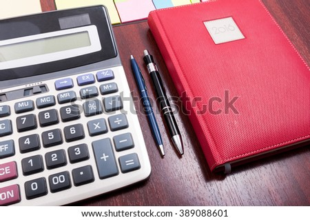 Wooden desktop with red agenda and calculator as bookkeeping and business financial concept - stock photo