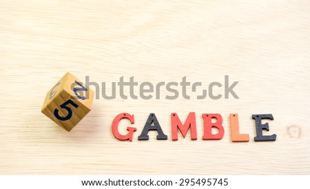 Wooden dice on a wooden table surface with alphabet GAMBLE. Concept of luck, chance, gamble and probability. Copy space. - stock photo