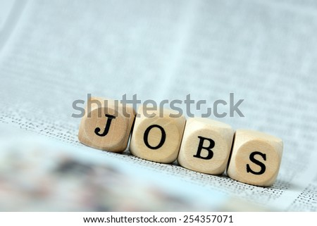 Wooden dice with the word Jobs on a newspaper / Job - stock photo