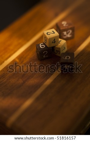 Wooden dices with numbers on wooden surface. - stock photo