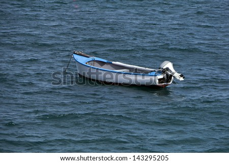 Wooden dinghy at anchor; single clinker-built dingy with outboard motor; good copy space  - stock photo
