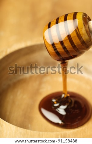 Wooden dipper covered with light golden honey - stock photo