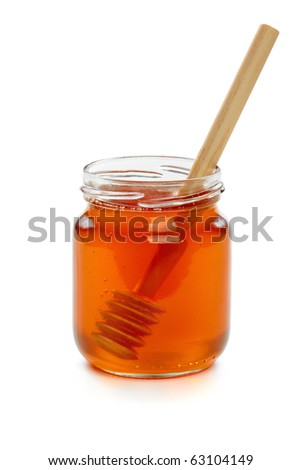Wooden dipper with jar of honey, isolated on the white background, clipping path included. - stock photo