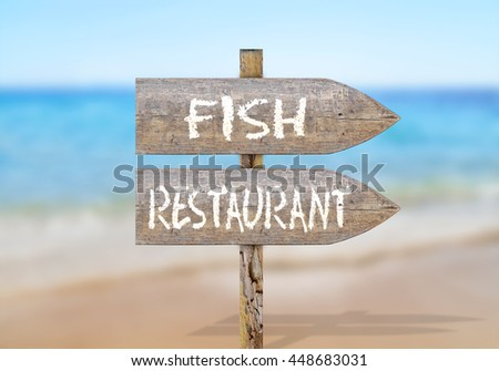 Wooden direction sign with fish restaurant - stock photo