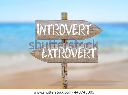 Wooden direction sign with introvert and extrovert - stock photo