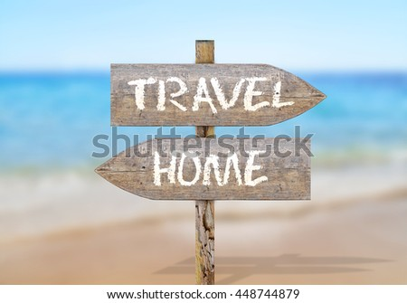Wooden direction sign with travel and home - stock photo