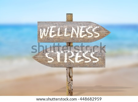 Wooden direction sign with wellness and stress - stock photo