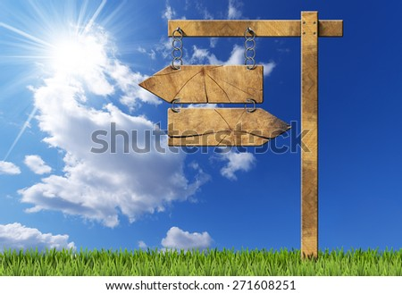 Wooden directional sign with two empty arrows in opposite direction hanging with a metal chain on a wooden pole on blue sky with clouds, sun rays and green grass - stock photo