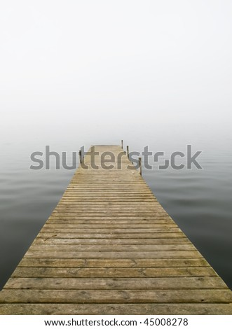 Wooden dock in a lake. Photo taken in a misty day - stock photo