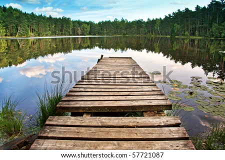Wooden dock on beautiful forest lake - stock photo
