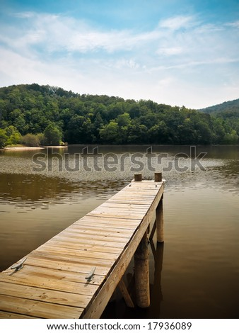 Wooden Dock Overlooking Peaceful Mountain Lake with bold blue and gold color in the water and sky.