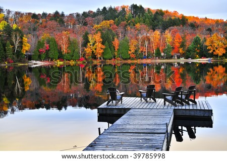 Wooden dock with chairs on calm fall lake - stock photo