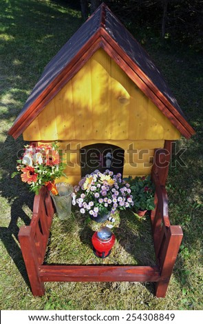 Wooden dog house as a monument on the grave - stock photo