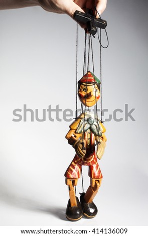 Wooden doll marionette of Pinocchio liar with big nose isolated on background - stock photo