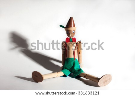 Wooden doll of Pinocchio liar with big nose and shadows on white background - stock photo