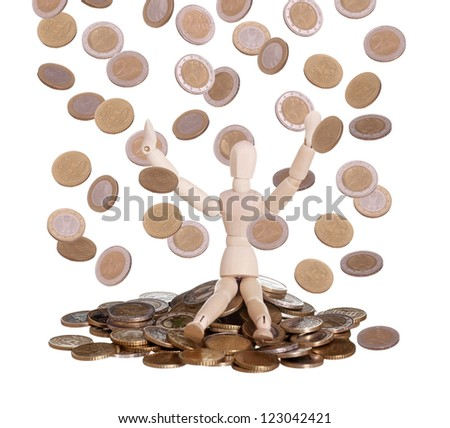 wooden doll sitting in rain of coins - stock photo