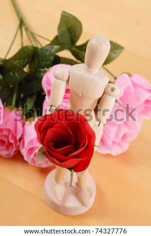 Wooden Doll with Red Rose Asking For Forgiveness - stock photo